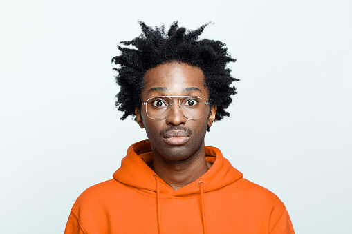 Shocked afro american young man wearing orange hoodie and glasses, staring at camera. Studio shot on grey background.