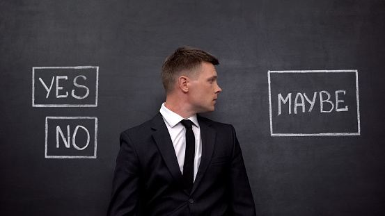 506662064 istock photo Confused man in suit doubting between yes, no and maybe buttons on blackboard 1183376258