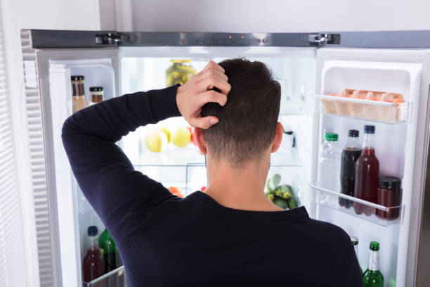 confused man looking at food in refrigerator - eating technology stock photos and pictures