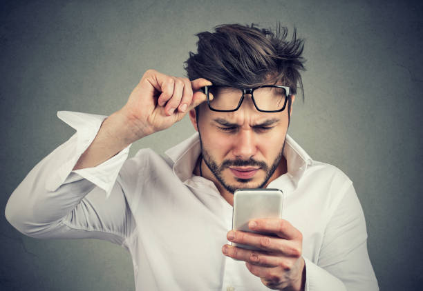Confused man reading phone with difficulties stock photo