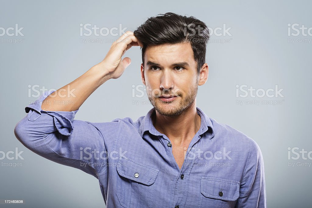 Confused man scratching his head royalty-free stock photo