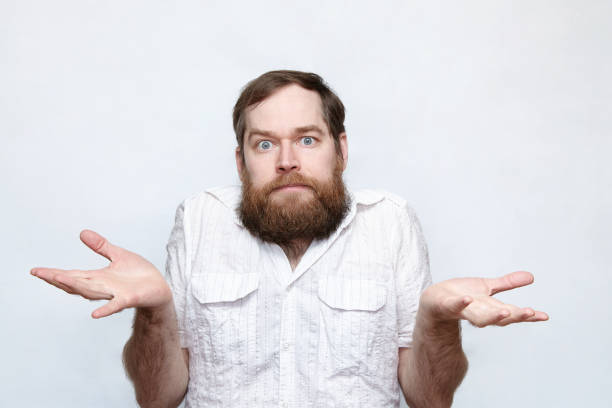 Confused man shrugging shoulders over gray background stock photo