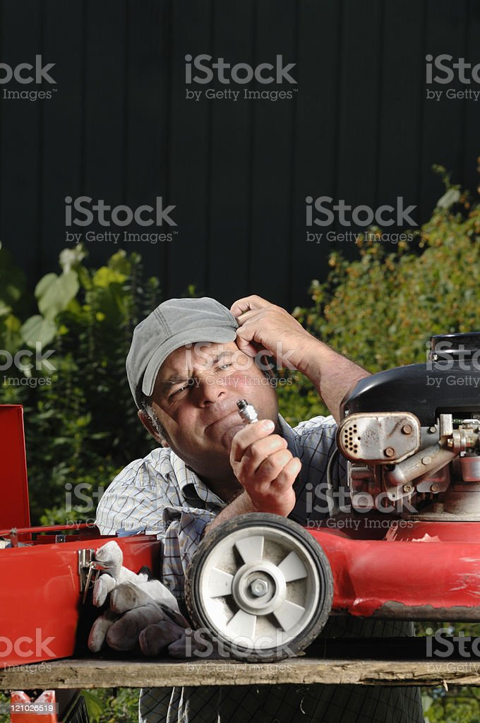 Confused man trying to fix a broken lawnmower stock photo