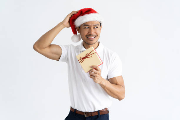 5c0de2e54bb40 Confused man wearing Santa hat and holding gift box stock photo