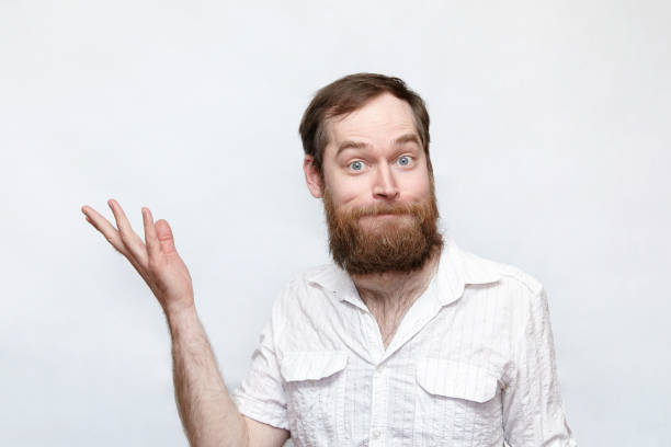 Confused man with hand raised over gray background stock photo