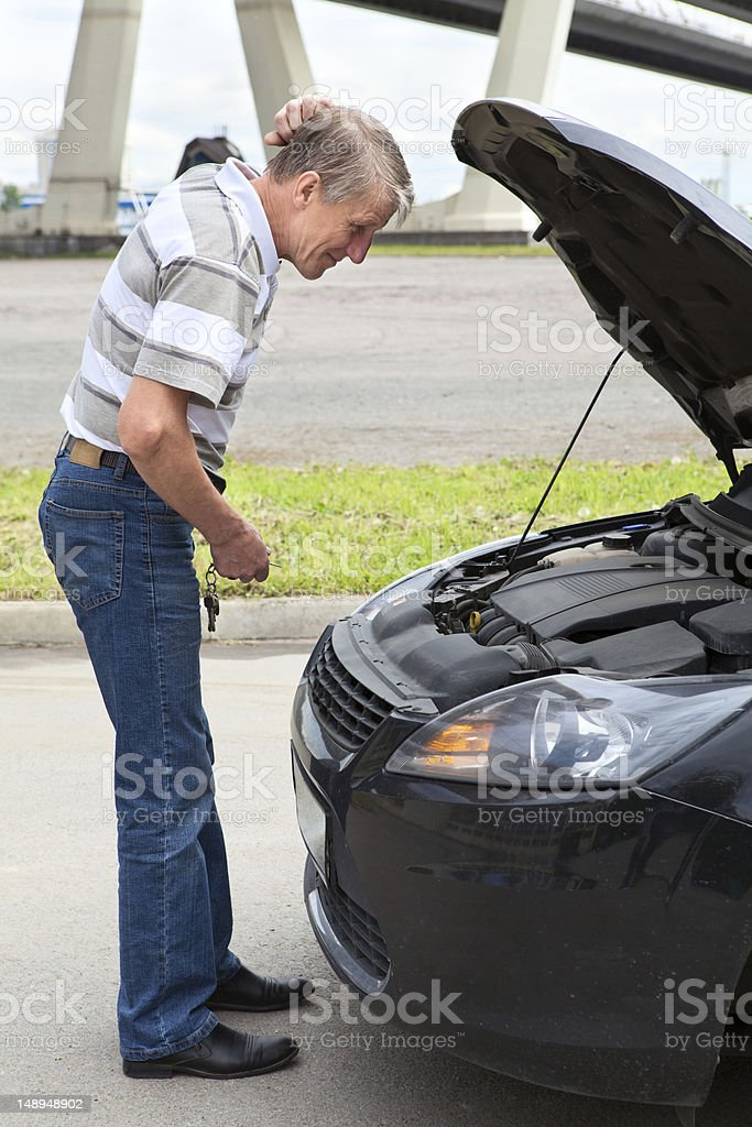 Confused mature driver with opened engine hood royalty-free stock photo