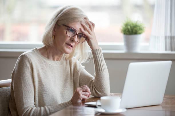 verwirrt reife frau denken online-problem blick auf laptop - frustration stock-fotos und bilder