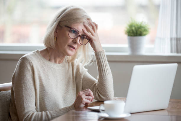 confused mature woman thinking about online problem looking at laptop - discontented stock pictures, royalty-free photos & images