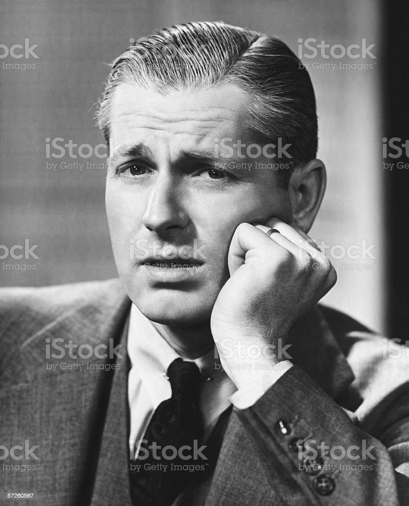 Confused mid-adult man indoors, (B&W), portrait royalty-free stock photo