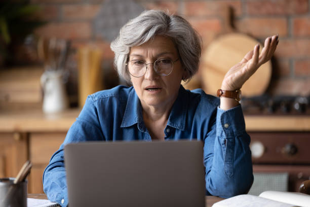 Confused middle aged woman in glasses looking at computer screen. stock photo