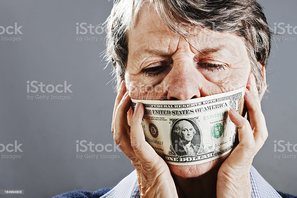 Confused old woman closes her eyes to dollar bill gag stock photo