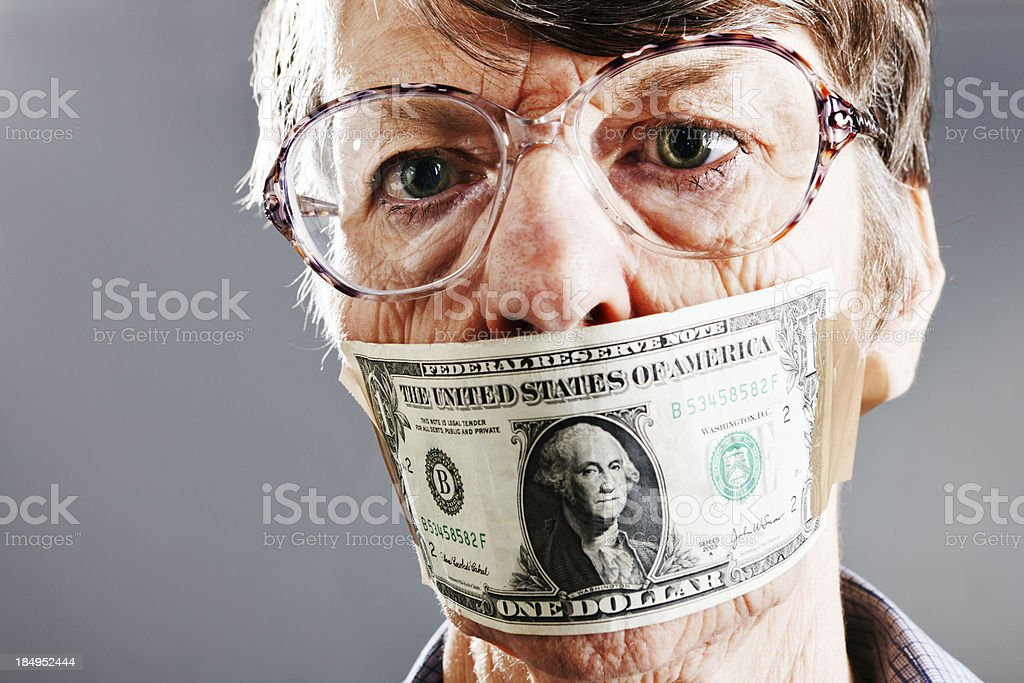 Confused old woman gagged with dollar bill wonders why stock photo