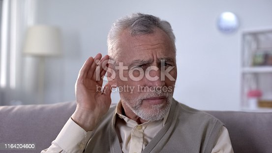 1029343276istockphoto Confused pensioner trying to hear conversation, problem of deafness in old age 1164204600