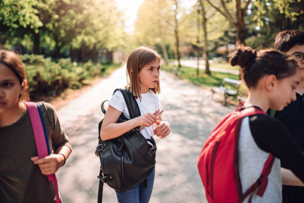 confused schoolgirl standing in schoolyard with classmates - disbarment stock pictures, royalty-free photos & images