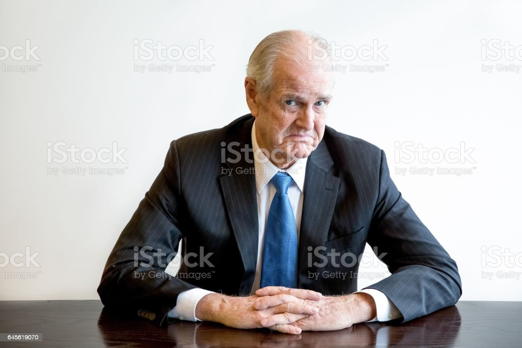 Confused senior business executive sitting at desk stock photo