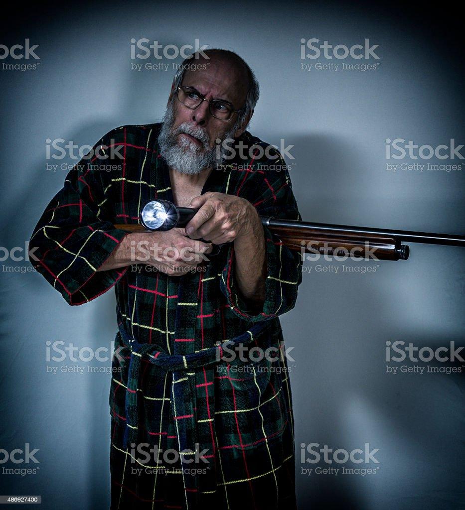 Confused Senior Man Holding Shotgun Pointing Flashlight in Dark Room stock photo