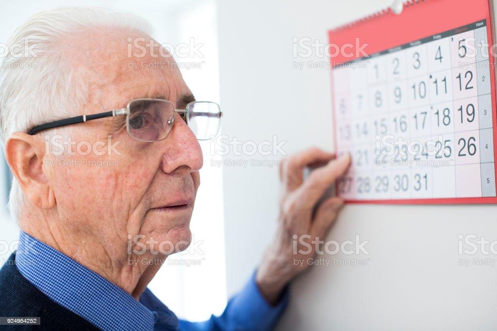 Verwirrt Senior Mann mit Demenz schaut an Wand Kalender – Foto