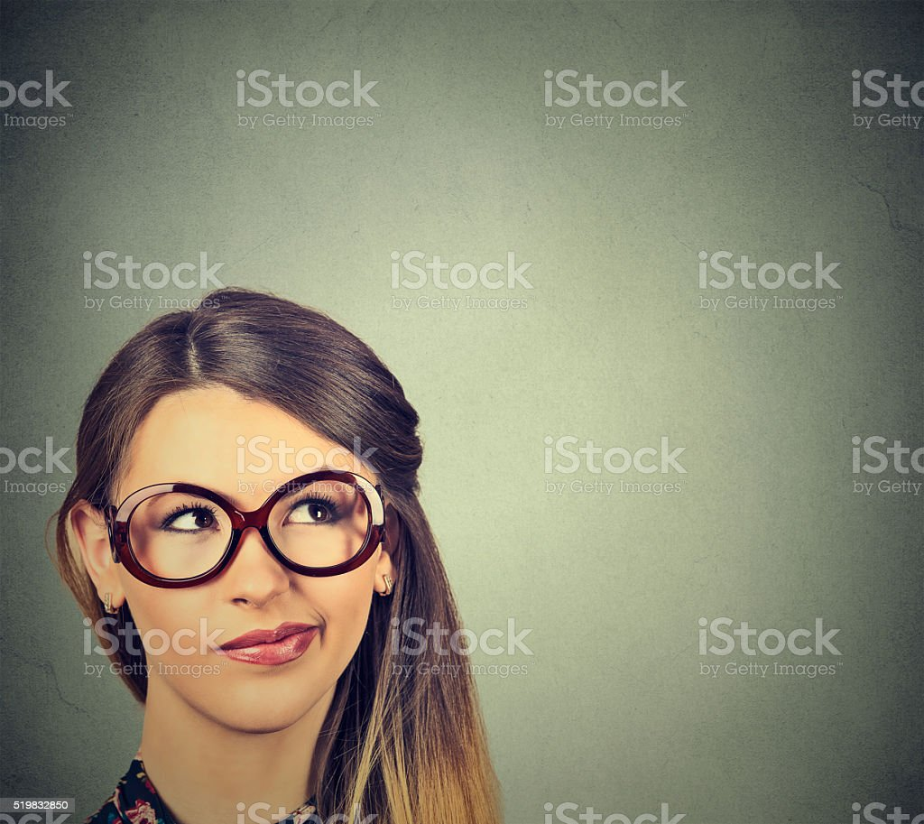 Confused skeptical woman in glasses thinking planning looking up stock photo