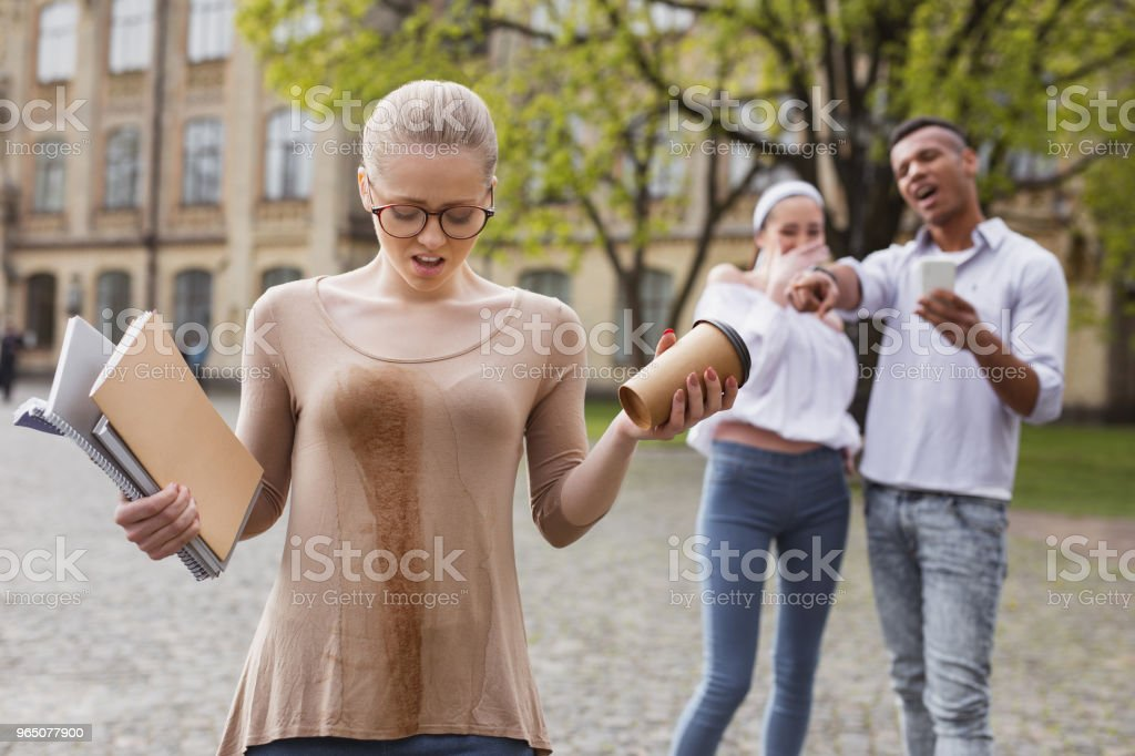Confused student feeling awful after spilling tea on her clothes royalty-free stock photo