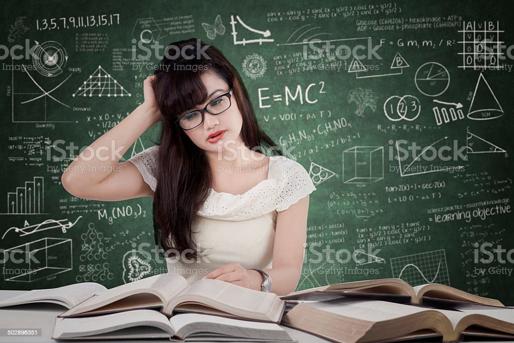 Confused student reading many books stock photo