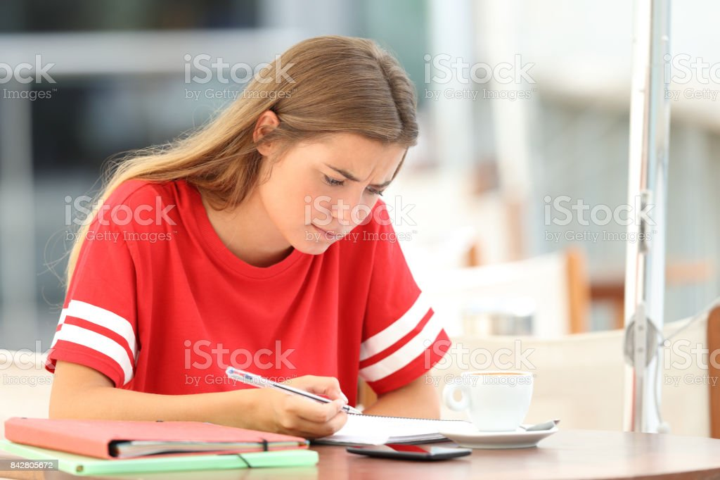 Confused student studying in a coffee shop stock photo