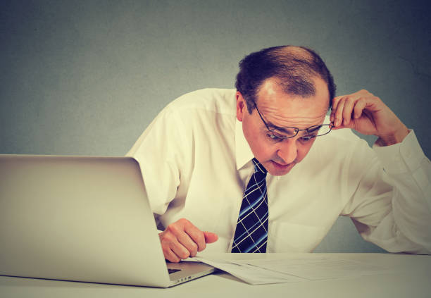 Confused surprised business man looking at documents. Shocked corporate middle aged executive working at his desk in office reviewing paperwork stock photo