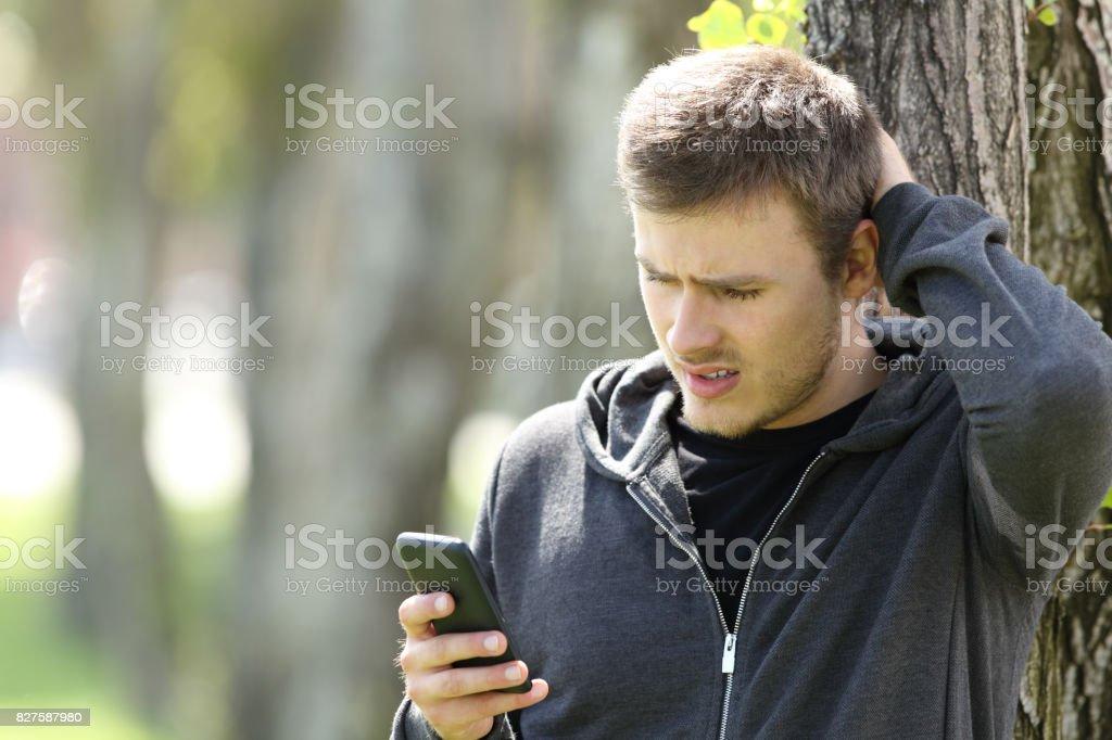 Adolescente confundido leer mensaje en un teléfono inteligente - foto de stock