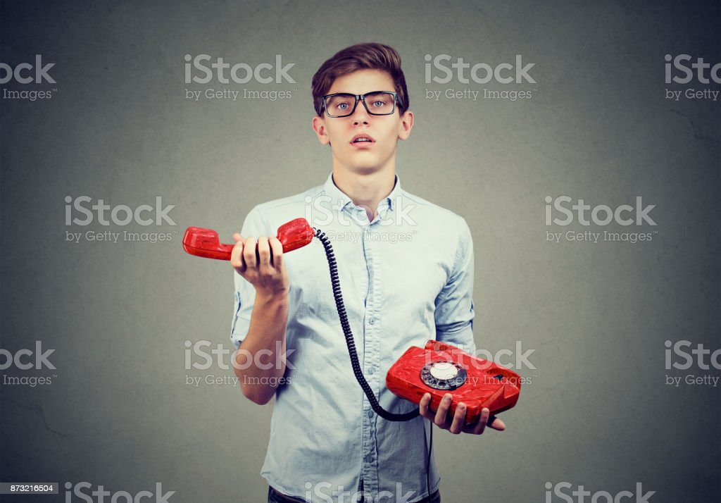 Confused teenager man with old fashioned telephone stock photo