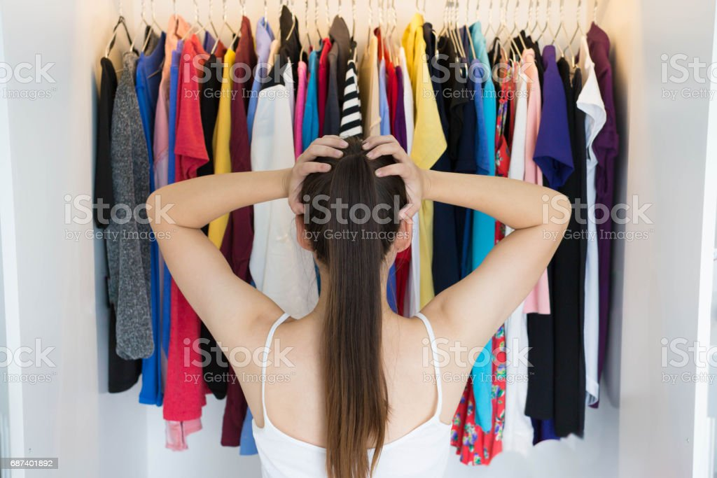 Confused woman choosing what to wear in front of her wardrobe stock photo