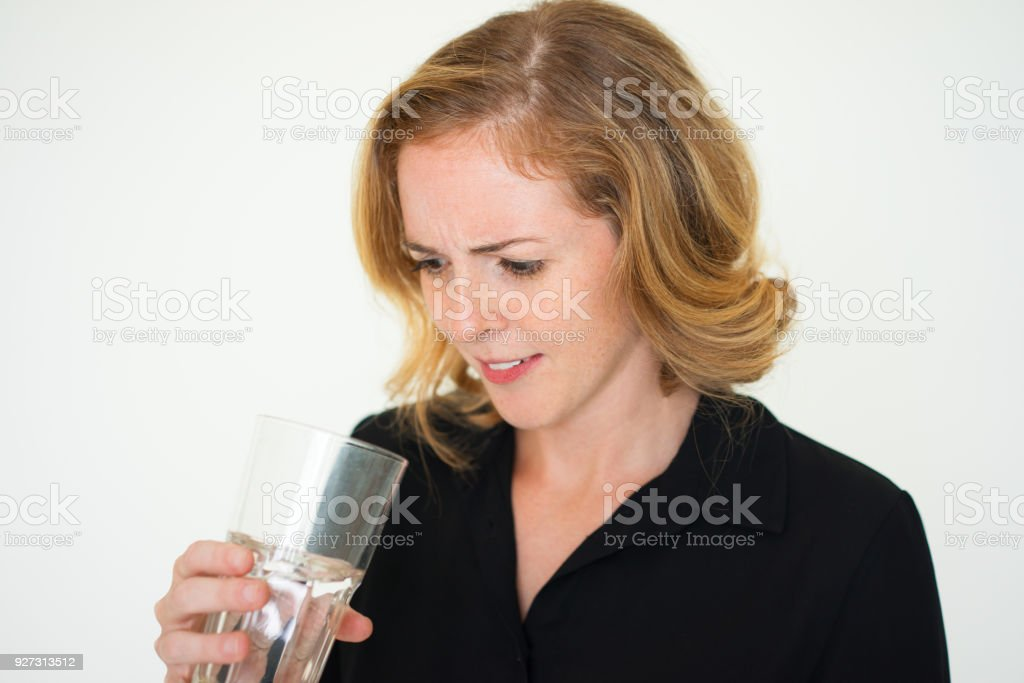 Confused woman examining water in glass stock photo