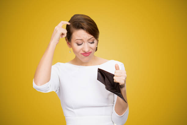 Confused woman having empty wallet Young woman scratching in head and looking inside of empty wallet having no money empty wallet stock pictures, royalty-free photos & images