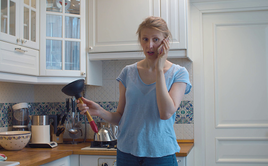 Confused woman in the kitchen with a plunger in her hands. She is calling by smart phone for advice. Kitchen sink clogging. Plumbing in need of repair. Housekeeping