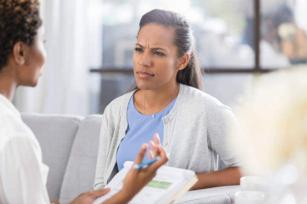 Confused woman listens to counselor stock photo