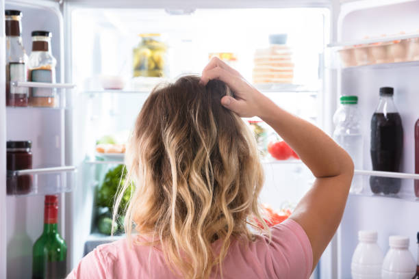 Confused Woman Looking In Open Refrigerator Rear View Of A Confused Woman Looking In Open Refrigerator At Home hungry stock pictures, royalty-free photos & images