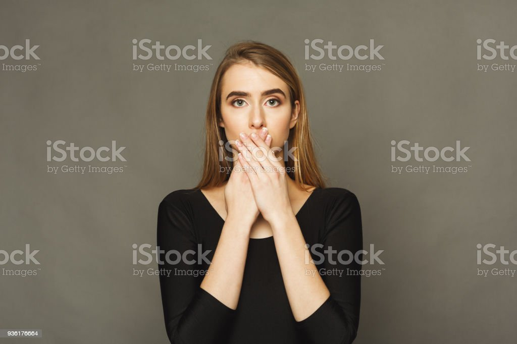 Confused woman puts her hands on lips. - Royalty-free Adult Stock Photo