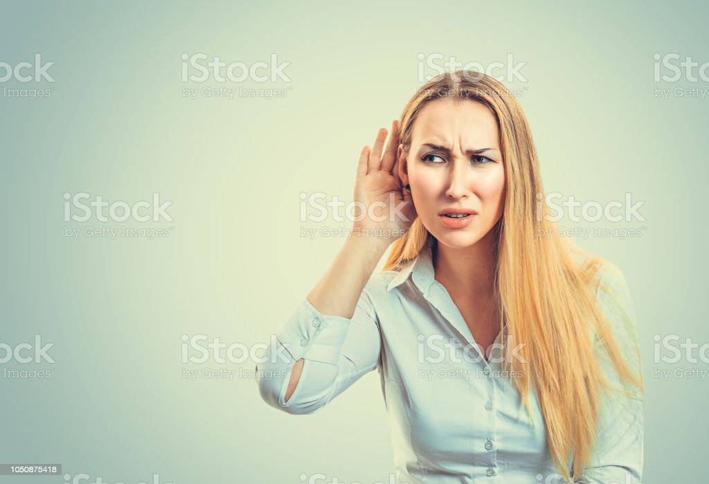 Confused woman trying to hear distinctly stock photo