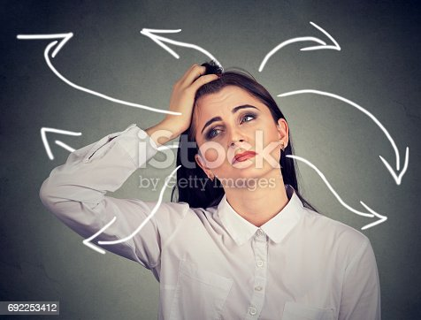istock Confused woman with many twisted arrows coming out of her head 692253412