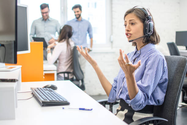 Confused young call center worker shrugging shoulders and looking at computer screen in office stock photo