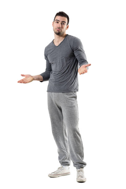 confused young fit sporty man shrugging shoulders looking at camera - sweatpants stock-fotos und bilder