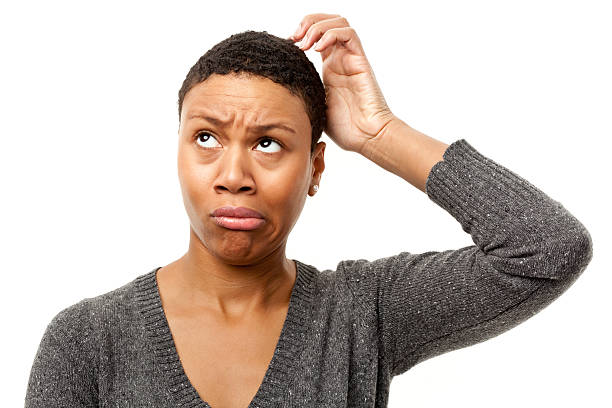 Confused Young Woman Scratching Head stock photo
