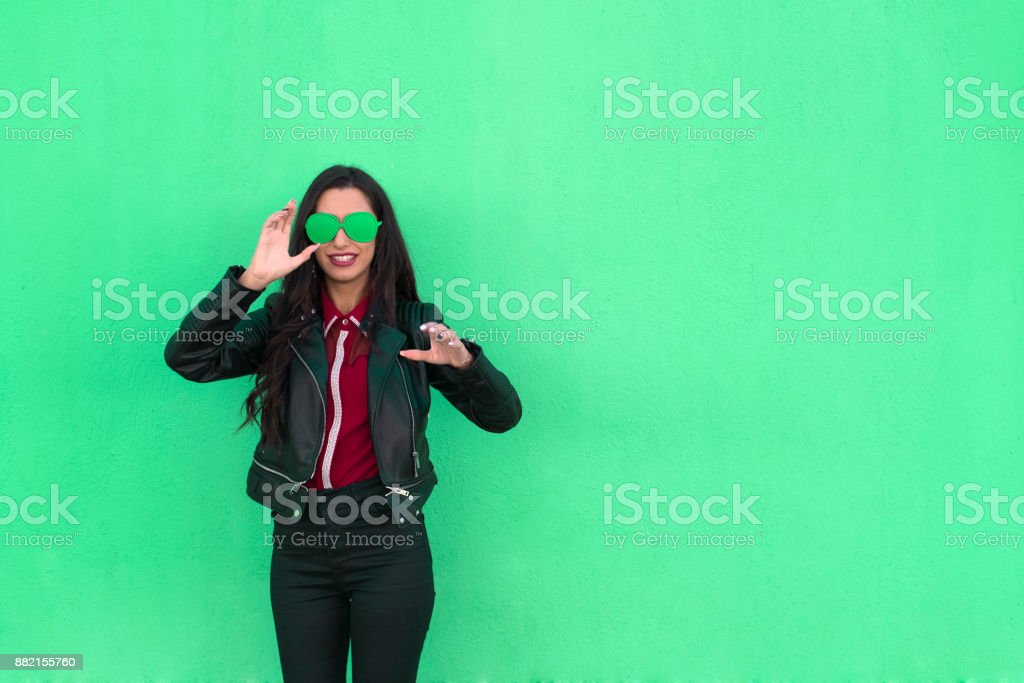 Confused young woman smiling on green background stock photo