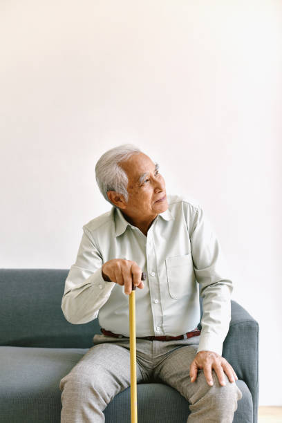 Confusing and forgetful elderly asian man with thinking gesture, Alzheimer's disease, Dementia cognitive brain problem in old pensioner, Senior healthcare concept. stock photo