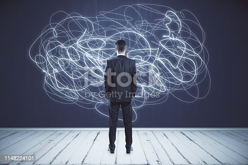 Back view of thoughtful young businessman looking at abstract scribble on wall. Confusion and doubt concept