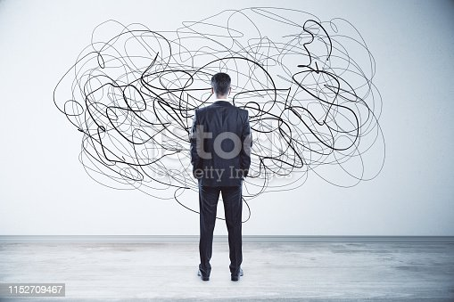 Back view of thoughtful young businessman looking at abstract scribble on wall. Confusion and think concept