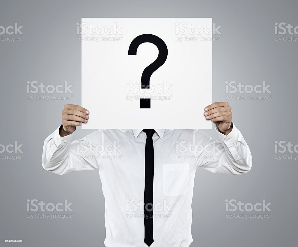Confusion Young businessman holding white card with question mark on it isolated on gray background Adult Stock Photo