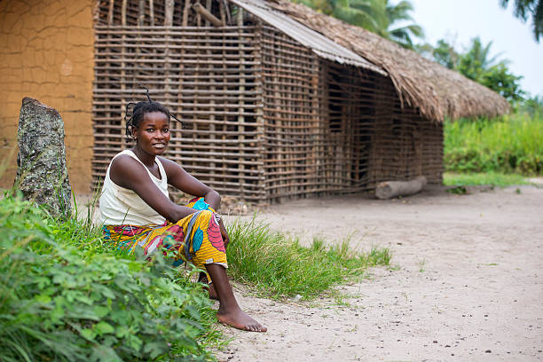 congolese woman is sitting in front of her house - democratic republic of the congo stock photos and pictures