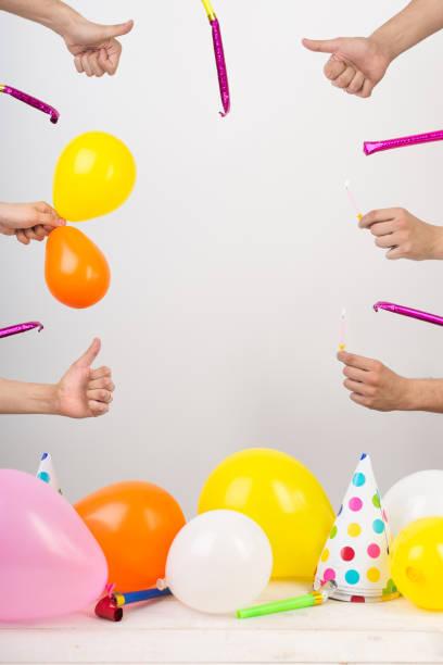gratulation, spaß, jubiläums-konzept. muster für karte mit rahmen von waffen mit daumen nach oben und pfeifen, im unteren teil des fotos es sind ballons und partyhüte. negativer raum für text - einladungskarten kostenlos stock-fotos und bilder