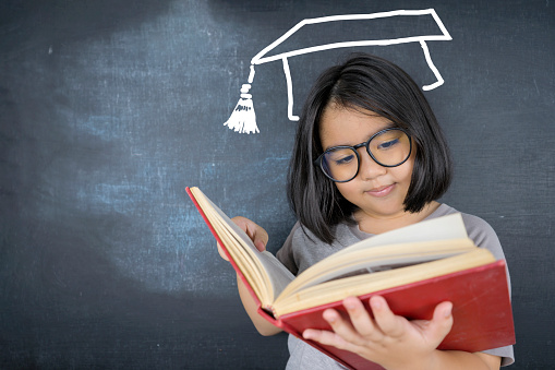 The cute girl wearing glasses is standing reading a book and she is congratulations graduates cap on blackboard, concept of education.