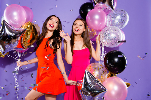 Congratulations, greeting, feast, nightlife concept. Two winsome person with modern hairdro in fuchsia, red formalwear isolated on shine purple background enjoy midnight countdown raised hands up