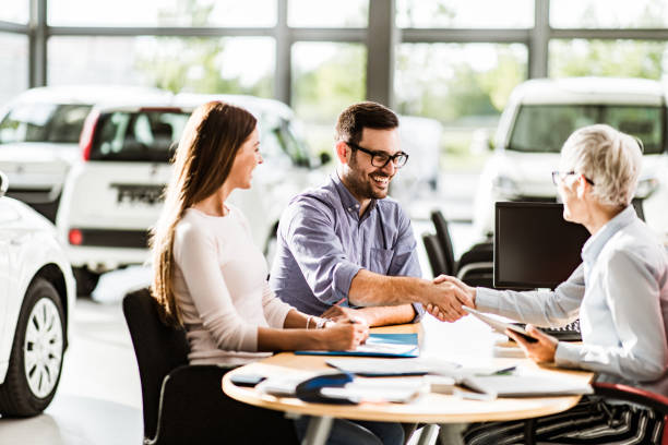 Congratulations, we have a deal about buying a car! Happy couple came to an agreement with car salesperson on a meeting in a showroom. Focus is on man. car salesperson stock pictures, royalty-free photos & images